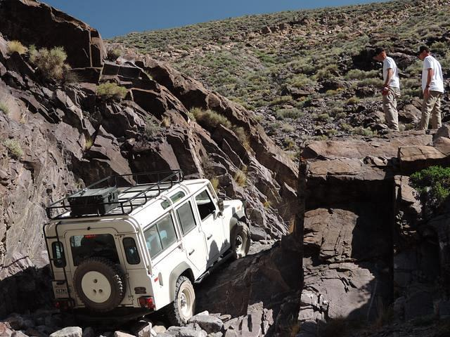 The land rover has to be winched up the waterfall.